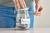 Woman Hand Holding Us Dollar Bill And Putting In A Glass Jar With Inscription Saving. Saving Money A poster