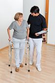 stock photo of zimmer frame  - Full length of a trainer holding clipboard and looking at senior woman using walker - JPG