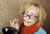 image of tawdry  - Crazy woman with crossed eyes drinking wine through a straw - JPG