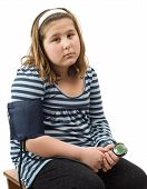 image of bp  - A young girl sitting on a stool getting her blood pressure taken isolated against a white background - JPG