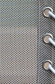 stock photo of grommets  - vertical orientation close up of woven fabric with grommets and plenty of copy space - JPG