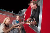 stock photo of take out pizza  - Chef serving carryout pizza from food truck - JPG