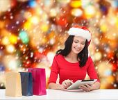 christmas, x-mas, online shopping, electronics concept - smiling woman in santa helper hat with shop