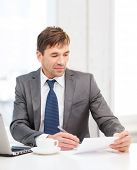 technology, business, education and office concept - handsome businessman working with laptop computer and documents