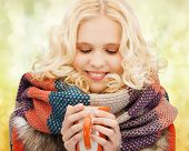 winter, people, happiness, drink and food concept - smiling teenage girl in warm clothes with tea or coffee mug