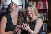 Two Elegant Women Laughing At A Text Message