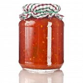 delicious product of roasted red pepper, tomatoes  in glass jar close up isolated on a white background