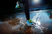 stock photo of rain  - Single runner running in rain and making splash in puddle - JPG