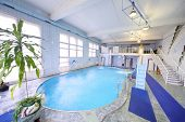 Empty oval indoor swimming pool with a small slide and clean water