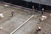 workers make metal reinforcement for the concrete foundation