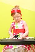 Mod little girl in a bright lush dress playing on a toy piano