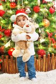 Picture of happy small boy holding teddy bear in hands on beautiful decorated Christmas tree background, little child wearing red Santa Claus hat, New Year celebration, child's xmas party