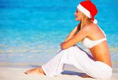 Christmas holidays on Maldives,  pretty female on the beach wearing Santa Claus hat, side view, travel and vacation concept