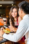Asian Chinese couple - Man and woman - or lovers flirting and having a date or romantic dinner in a
