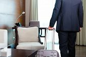 Manager or businessman on a business trip arriving to hotel room or suite after check-in with his trolley