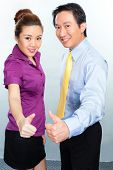 Motivated Asian business employees or colleagues giving thumbs up for optimistic atmosphere
