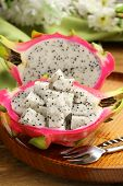 stock photo of dragon fruit  - ripe sweet tropical dragon fruit on a wooden plate - JPG
