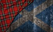 pic of kilts  - tartan textile on wooden background with scotland flag - JPG