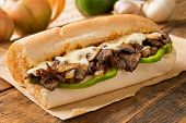 stock photo of lunch  - A delicious oven baked steak and cheese submarine sandwich with mushrooms green peppers and onion - JPG