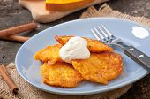 Pumpkin Fritters with cinnamon and sugar on the old wooden background
