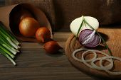 Different raw onion on wooden background