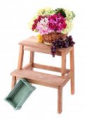 Wicker basket with flowers and fruits,  on small wooden ladder, isolated on white