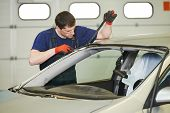 Automobile glazier worker disassembling windscreen or windshield of a car in auto service station garage before installation