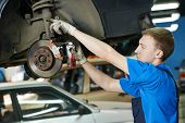 picture of adjustable-spanner  - car mechanic replacing car wheel brake shoes of lifted automobile at repair service station - JPG