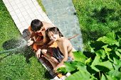 Happy kids playing and splashing with water sprinkler on summer grass yard