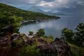 Calm lagoon with wet land and mountains on the background at rainy day. Bali, Indonesia