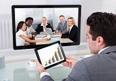 pic of video chat  - Young Businessman Analyzing Graph While Chatting With His Colleagues - JPG