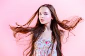 Elegant girl with natural make-up and beautiful long hair in motion posing over pink background. Fas