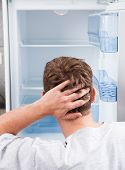 stock photo of refrigerator  - Portrait of thoughtful man looking in empty refrigerator - JPG