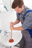 Portrait Of Male Plumber Pressing Plunger