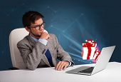 Handsome young man sitting at desk and typing on laptop with present boxes icons