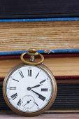 antique clock on books background