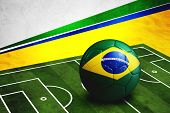stock photo of nationalism  - Soccer ball with Brazil flag on soccer pitch - JPG