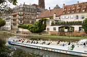 Strasbourg's Cityscape With The Ill River And A Touristic Boat
