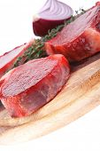 fresh raw beef fillet medallions with thyme twig on wooden plate isolated over white background