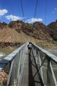 pic of zoroaster  - a woman hikes across silver bridge over the Colorado River at the bottom of the Grand Canyon Arizona