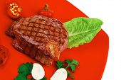 barbecued meat : beef ( lamb ) garnished with green lettuce and red chili hot pepper on red plate is