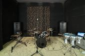 Studio room with drum set, microphones and recording equipment.