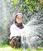 Beautiful Middle Eastern Arabic girl having happy time in summer garden with water sprinkle