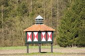 Dovecote In Meadow Against Forest
