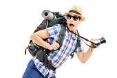Scared hiker with backpack and camera running away isolated on white background