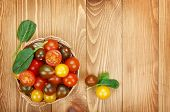 Colorful cherry tomatoes on wooden table background with copy space