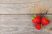 Ripe strawberries over wooden table background with copy space