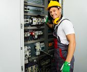 Cheerful electrician in a safety hat on a factory