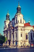 Vintage retro hipster style travel image of St. Nicholas church at Old Town Square early in morning,