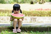 stock photo of melon  - Little child with sunglasses and big slice of watermelon sitting in the park